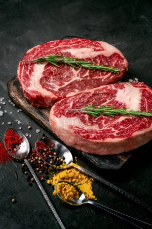 Photo for Two raw rib eye steak with seasonings on the dark stone background prepared for cooking. Marbled beef top view - Royalty Free Image