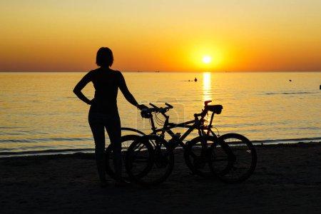 Photo pour Silhouette de femme avec le vélo au coucher du soleil par la mer Baltique - image libre de droit