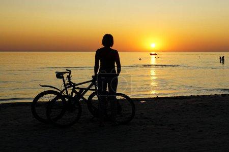 Photo pour Silhouette de femme avec le vélo au coucher du soleil au bord de la mer - image libre de droit