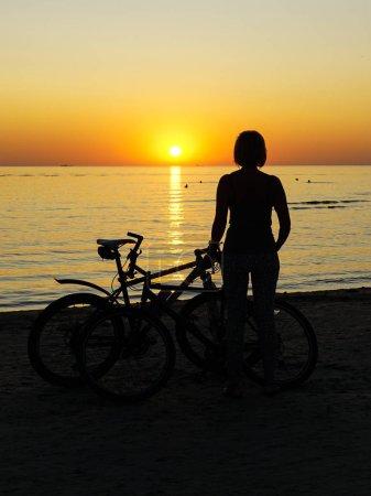 Photo pour Silhouette femme avec vélo au coucher du soleil au bord de la mer - image libre de droit