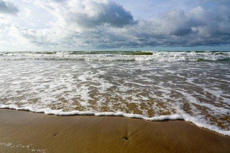 Photo pour Le littoral de la mer Baltique avec du sable brun et un ciel nuageux - image libre de droit