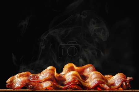 Pile of steaming hot freshly cooked bacon with room for text in black background