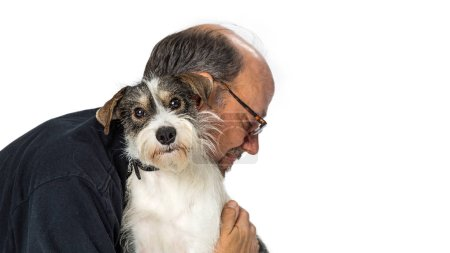 Adult male hugging a cute wire-haired nixed small terrier breed dog that is looking at the camera over white