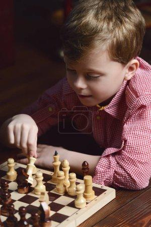 Foto de Niño jugando al ajedrez en casa. Juegos y actividades para los niños. Concepto de familia - Imagen libre de derechos
