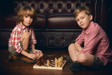 Foto de Dos niños están jugando al ajedrez en casa. Juegos y actividades para los niños. Concepto de familia - Imagen libre de derechos