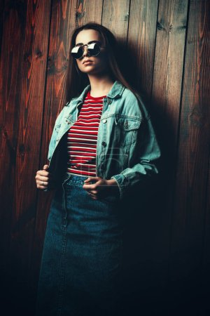 Photo for Modern young woman in denim jacket, trendy sunglasses and red t-shirt stands by a wooden wall. Youth style. - Royalty Free Image