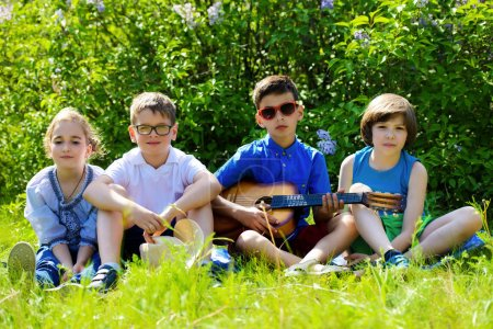 Group of cheerful children resting in the park with songs and guitar. Outdoor activity. Summer holidays.