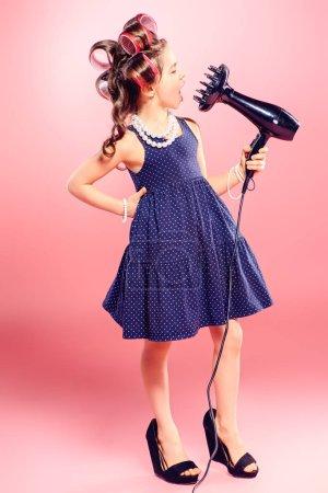 Photo pour Portrait d'une jolie petite fille avec des bigoudis dans les cheveux tenant les cheveux sèche. Studio tourné sur fond rose. Mode pour enfants. - image libre de droit