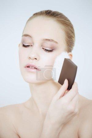 Photo pour Gros plan portrait d'une belle jeune femme appliquant un pinceau de maquillage. Beauté, maquillage cosmétique . - image libre de droit