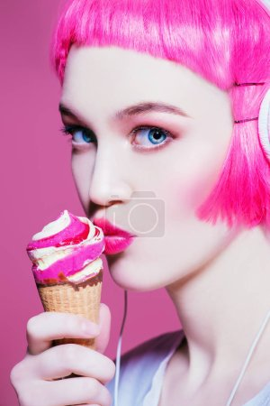Photo for Trendy girl with pink hair wearing headphones is eating ice cream. Pink background. Youth style, leisure. - Royalty Free Image