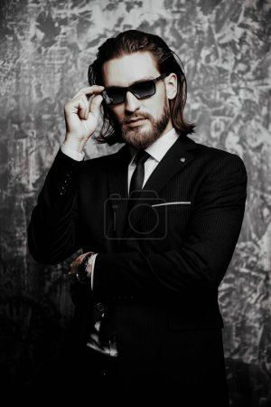 Photo for Fashion shot. Handsome young man posing in elegant suit and sunglasses over dark background. Men's beauty, fashion. - Royalty Free Image