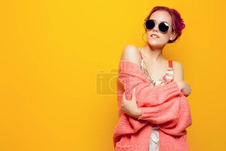 Beautiful girl with pink hair wearing bright clothes over yellow background. Bright style, fashion.