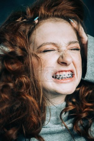 Expressive teen girl wearing dental braces. Emotions. Stomatology and orthodontics.