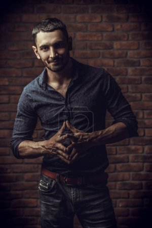 Photo for Portrait of a handsome brunet man standing by a brick wall. Men's beauty, fashion. Men's barbershop, Hairstyle. - Royalty Free Image