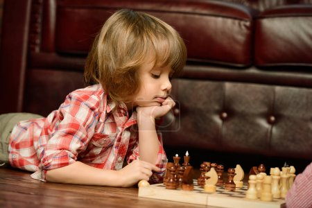 Photo pour Petit garçon jouant aux échecs à la maison. Jeux et activités pour les enfants. Concept de famille . - image libre de droit