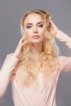 Portrait of a beautiful woman with blonde long hair. Beauty, haircare, cosmetics concept. Healthcare. Gray background.