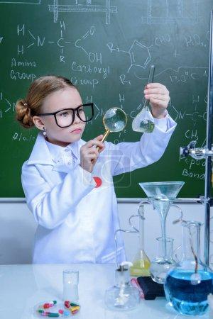 Photo pour Fillette grave faire des expériences en laboratoire. Enseignement des sciences et. - image libre de droit