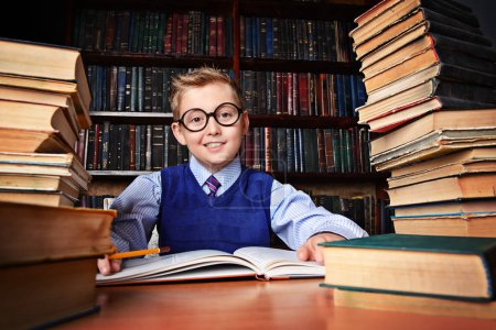 Smart boy in a suit sitting in the library by the bookshelves with many old books. Educational concept. Science.