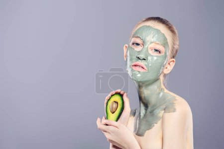 Beautiful spa woman in facial mask and avocados. Beauty, natural cosmetics concept. Spa, body care.