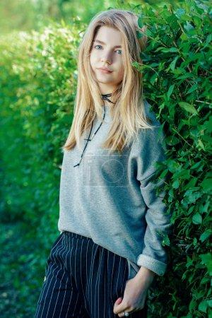 Portrait d'une fille ADO moderne avec longs cheveux blonds pose extérieure. Beauté, mode. Teen style