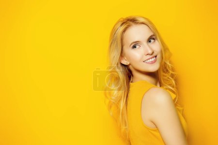 Beauty, fashion shot. Beautiful girl with a charming smile in a yellow dress on a yellow background. Blonde hair.