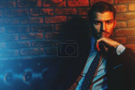 Photo pour Respectable bel homme en costume élégant, assis dans des appartements avec un intérieur luxueux classique. Beauté masculine, mode. - image libre de droit