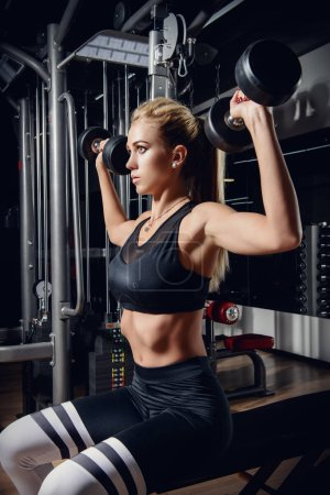 Beautiful athletic woman doing exercises with barbell in a gym. Healthy lifestyle. Sports, fitness, bodybuilding.