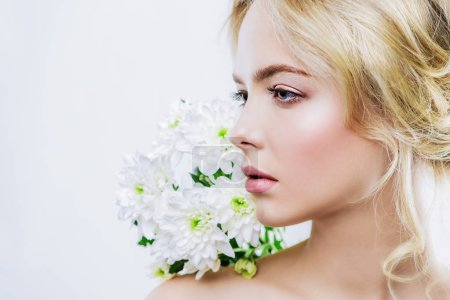 Close-up portrait of a beautiful romantic young woman with flowers. Copy space. Cosmetics, healthcare. Beauty, fashion concept.