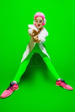Photo pour Portrait complet d'une fille à la mode aux cheveux roses portant des vêtements élégants et lumineux. Fond vert. Beauté, mode, style jeunesse . - image libre de droit