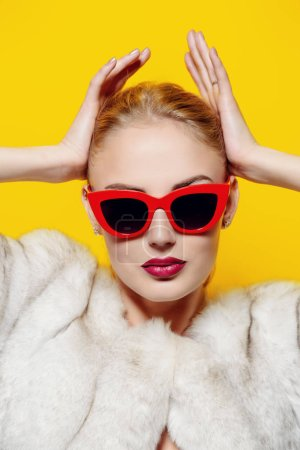 Gorgeous blonde woman posing in luxurious fur coat and pin-up sunglasses. Yellow background. Fashion, beauty. Studio shot.
