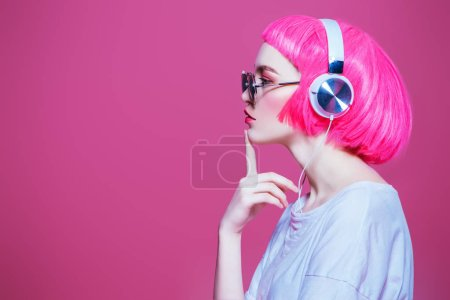 Photo for Trendy girl with pink hair wearing sunglasses enjoys the music on headphones. Pink background. Youth style, leisure. - Royalty Free Image