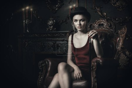 Gorgeous young woman in velvet red dress is sitting in the armchair in a luxury apartment. Classic vintage interior. Beauty, fashion.