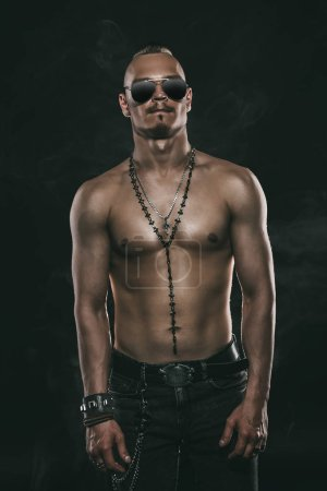 Portrait of a brutal handsome man with naked torso. Male beauty, health. Rocker, punk.