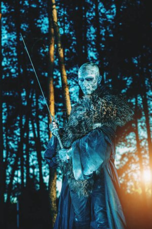 Zombie warrior in knightly armor stands in the night forest. Fantasy horror film. Halloween.