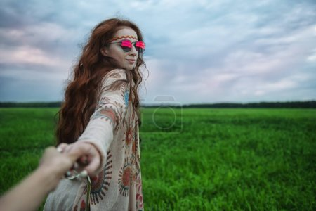 Photo for A portrait of a fashion female model holding a hand of the photographer. Contemporary bohemian style. Spirit of freedom. Fashion shot. Bohemian, bo-ho style. - Royalty Free Image