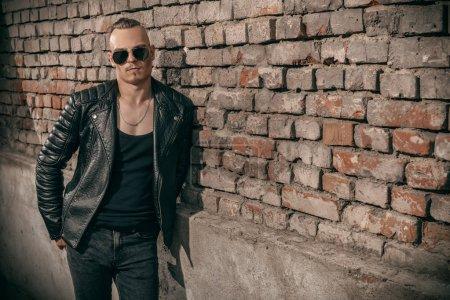 Portret punk człowiek na ulicy. Facet na podwórku. Moda, subkultura.