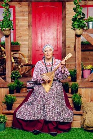 Foto de Mujer madura en traje étnico frente a una casa de madera. Retrato. Estilo rural, decoración - Imagen libre de derechos