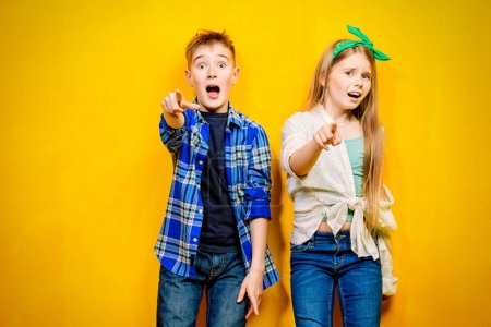 Children's fashion. Beautiful  little children posing at studio over yellow background. Laughing and happy.