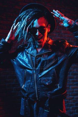 Photo pour Portrait d'un homme fou de disco avec des dreadlocks. Parti, disco. Lumière colorée. - image libre de droit