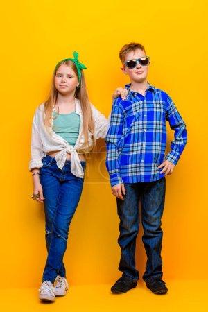 Photo pour Mode pour enfants. Beaux petits enfants posant en studio sur fond jaune. Riant et heureux . - image libre de droit