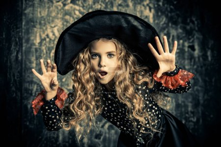 Beautiful child girl in a costume of a witch over grunge background. Halloween party.