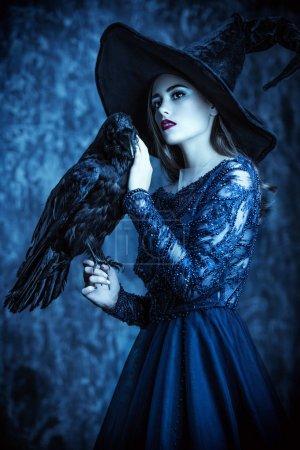 Photo pour Une sorcière avec un corbeau. Halloween. Célébration. - image libre de droit