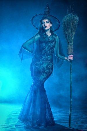 Photo pour Une belle dame dans un costume de sorcière tenant un balai. Halloween. Célébration. - image libre de droit