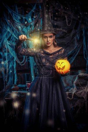 Photo pour Une sorcière dans un château tenant une lanterne et une citrouille. Halloween. Célébration. - image libre de droit