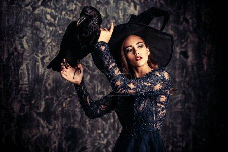 Photo pour Une sorcière dans le chapeau et la robe avec un corbeau. Halloween. Célébration. - image libre de droit