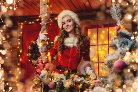 Smiling Santa girl in red body suit holds a gift box in her hands and poses near the house of Santa, decorated with festive lights. Christmas and New Year concept.