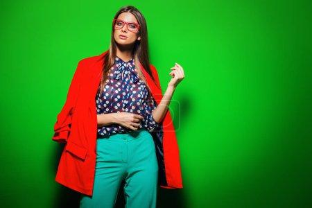 Photo pour Mode prise de vue. Belle femme sexy qui posent dans des vêtements lumineux sur fond vert. Beauté, concept de mode. - image libre de droit