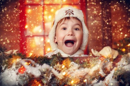 Happy cute child boy is standing near his house decorated for Christmas. Merry Christmas and Happy New Year.