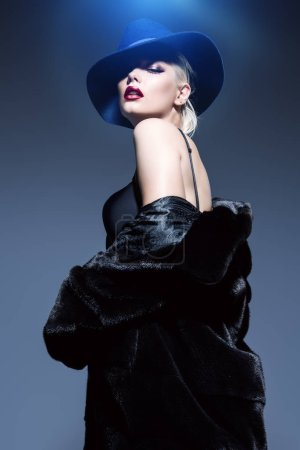 Photo pour Superbe femme blonde posant en manteau de fourrure luxueux et un chapeau. Mode, beauté. Plan studio . - image libre de droit