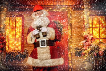 Photo for Santa Claus is a builder. House of Santa Claus. Portrait of Santa Claus in a helmet on his head standing near his decorated house and looks through binoculars. Christmas and New Year concept. - Royalty Free Image